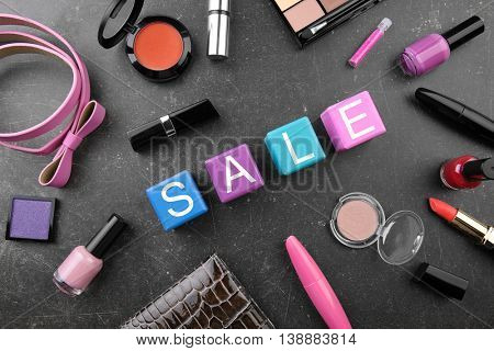 Sale concept. Wooden cubes with female stuff and cosmetics  on grey background