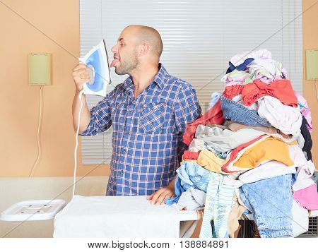 Caucasian Man Touches The Tongue Iron To Ironing Clothes.