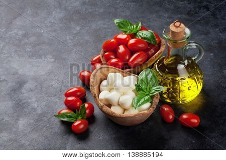 Mozzarella cheese, tomatoes and basil herb leaves over stone table. View with copy space