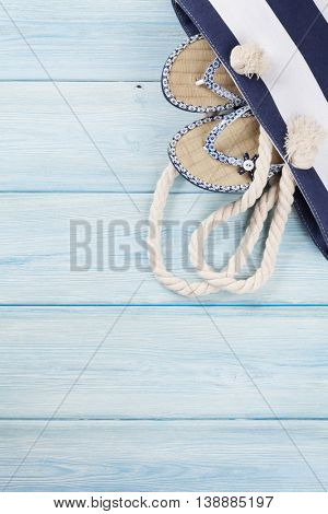 Beach accessories. Bag with flip-flops on wooden background. Top view with copy space