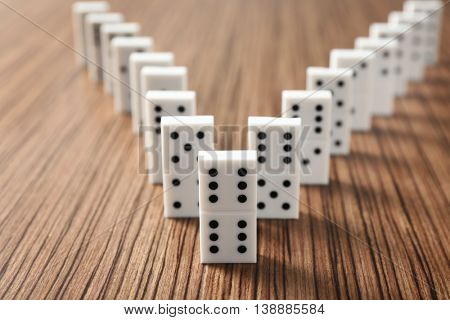 Row of dominoes on wooden table