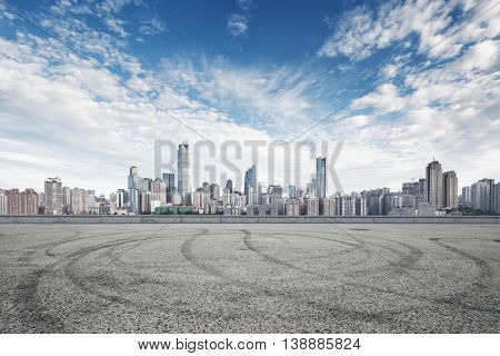 cityscape and skyline of chongqing in cloud sky on view from empty road with car tracks