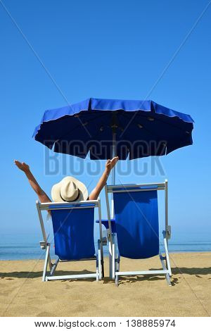 Girl lying on a sun lounger under an umbrella on sandy beach. Summer vacation by the sea.