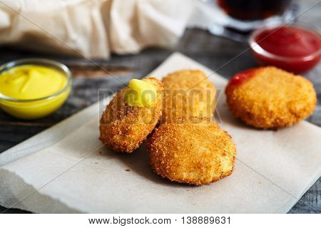 Homemade chicken nuggets on parchment paper with glass of cola and bowl with nuggets on background. Wood table.