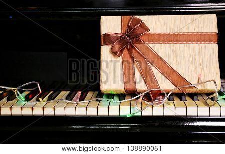Christmas gift box on piano keys, closeup