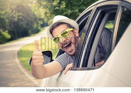Young man wearing hat and sunglasses showing thumbs up from driver's seat through opened window. Vacation and travel concepts.