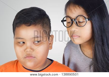 Portrait of young Asian girl grin and threaten small kid