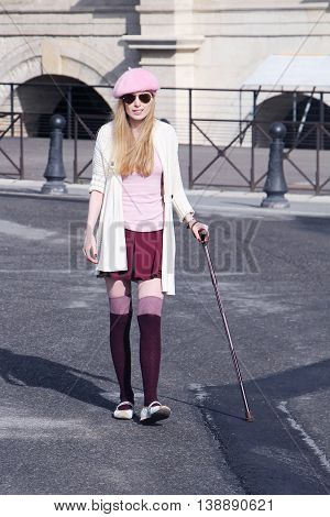 Young woman with injured leg walking with a stick
