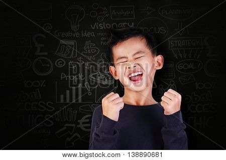 Success concept portrait of happy young Asian boy showing enthusiastic winning gesture shout with joy of victory over blackboard with business doodle scheme drawn on it
