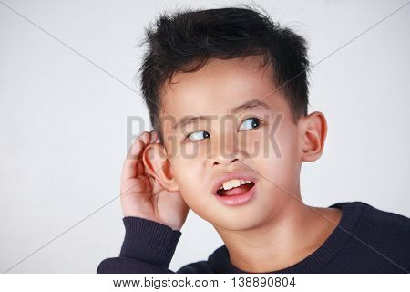 closeup portrait of young Asian boy listening carefully with his hand to ear gesture trying to hear secretly interesting information conversation news