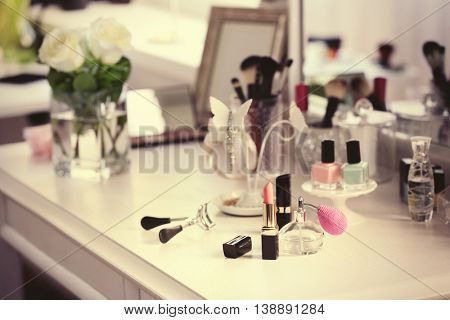 Lipstick with perfume bottle on light dressing table
