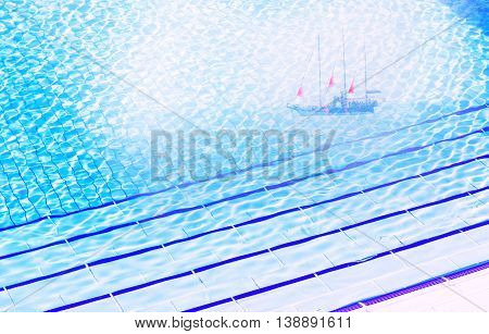 Clear blue water in pool at sunny day with dream about ship with scarlet sails like metaphore