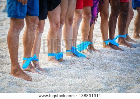 Group of people of different nationalities on the sand with legs connected by ribbon
