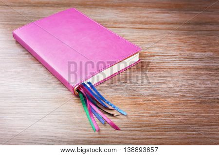 Notebook with bookmarks on wooden background