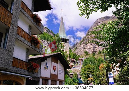 ZERMATT, SWITZERLAND - AUGUST 31, 2014: Saint Mauritius Church in the Background; Town Club (Meeting Place) in the Foreground on August 31, 2014 in Zermatt, Switzerland. Zermatt is a Mountain Resort Town in Southern Switzerland.
