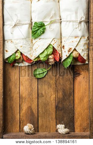 Healthy lunch snack. Three tortilla wraps with grilled chicken fillet and fresh vegetables on rustic wooden tray. Top view, copy space, vertical composition