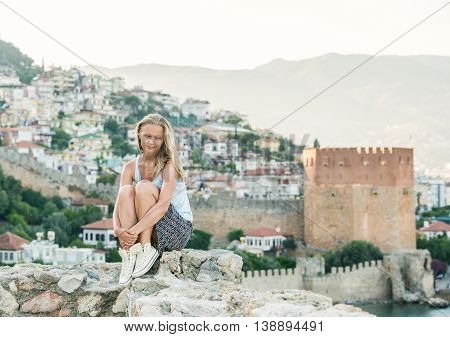 Young blond woman tourist relaxing on ancient fortress wall of Alanya castle. Kizil Kule or Red Tower at background. Turkey, Mediterranean region.