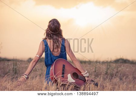 Young retro hippy styled woman with acoustic guitar in wheat field looking at sun to find inspiration for the next song. Music, art and lifestyle concepts.