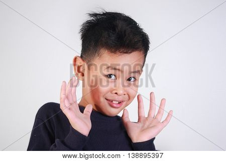 closeup portrait of young Asian boy being shocked of something and mocking gesture