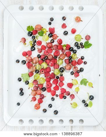 Fresh summer garden berries variety on white baking tray over white painted wooden backdrop, top view, vertical composition