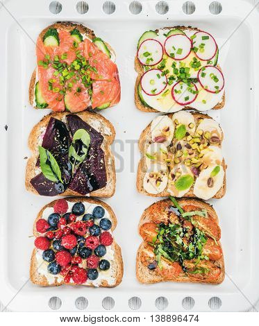 Sweet and savory breakfast toasts assortment. Sandwiches with fruit, vegetables, eggs and smoked salmon on white baking tray background, top view