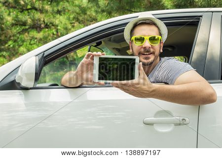 Young tourist guy showing white digital tablet device with blank display from driver's seat. Vacation and road map app concepts.