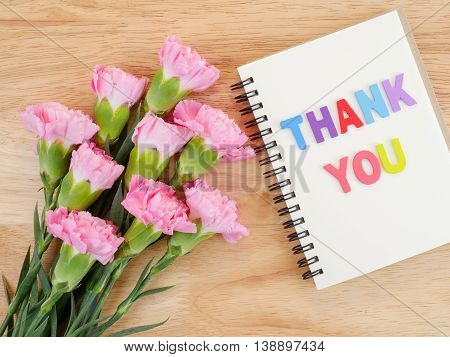 Word spell Thank you on notebook and bouquet of sweet pink Carnation flower on wood background with top view