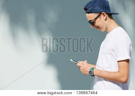 Side View Portrait Of Cute Teenage Boy Wearing White T-shirt And Sunglasses Typing A Message Using S