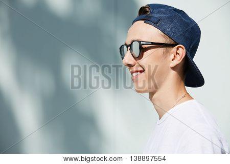 Close Up Profile Of Stylish Smiling High School Student Boy Wearing Shades And Snapback Backwards Po