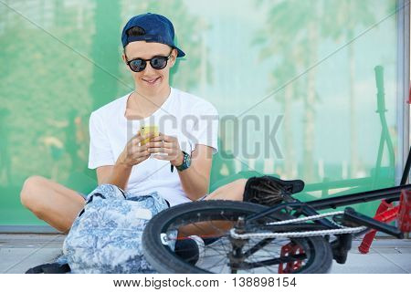 Smiling 15-year Old Schoolboy In Street Wear And Stylish Shades Messaging Via Social Networks With H