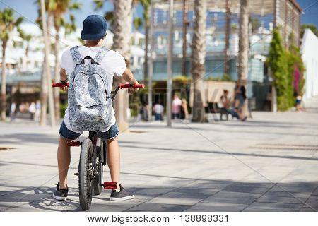 Rear View Of Teenager Boy In Street Wear, Carrying Backpack, Sitting In A Fixed Gear Bike, Having A