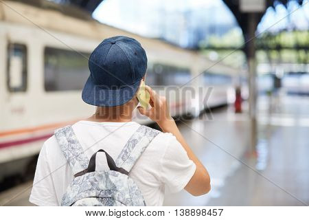 Rear View Of Schoolboy In Street Wear Talking On Mobile Phone, Discussing Plans For Summer Vacations