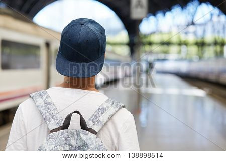 Back View Of Teenager Boy In Snapback Carrying Backpack While Returning Home After Classes At School