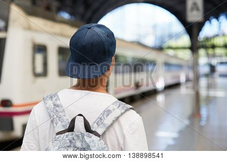 Rear View Of Caucasian Teenage Student Boy Carrying A Backpack, Walking On The Platform Of A Railway