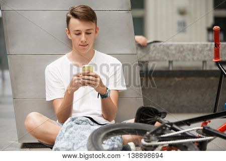 Portrait Of Caucasian High School Student In White T-shirt Surfing The Internet Using Free Wi-fi On