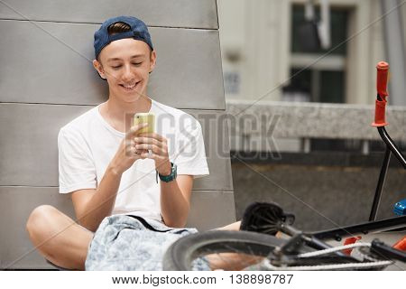 Happy Schoolboy Typing A Message On Mobile Phone, Sitting Outdoor Next To His Fixed Gear Bike. Teena