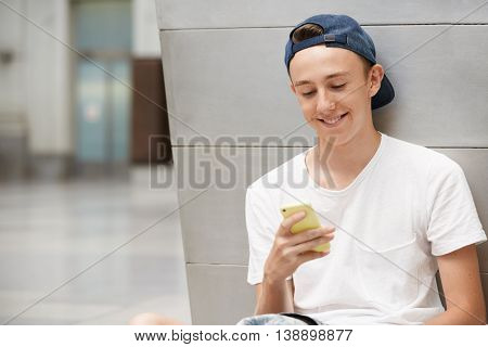 Happy Schoolboy Wearing White T-shirt And Snapback Backwards, Holding Cell Phone, Using Wireless Int