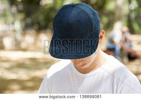 Close Up View Of Schoolboy Wearing Dark Blue Blank Snapback With Copy Space For Your Advertising Con