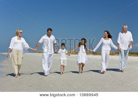 Three Generations Of Family Walking Holding Hands On Beach
