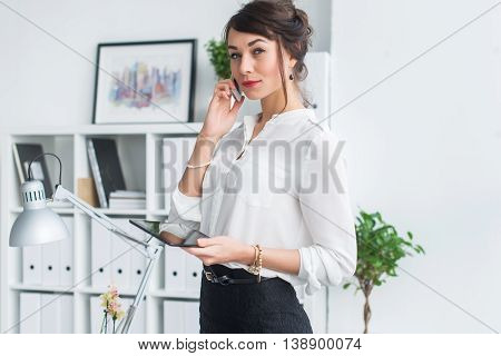 Portrait of a businesswoman having business call, discussing details, planning her meetings using diary and cellphone