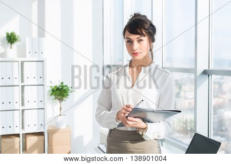 Beautiful, serious consultant wearing glasses and a formal office suit, holding her work stationary, looking at camera