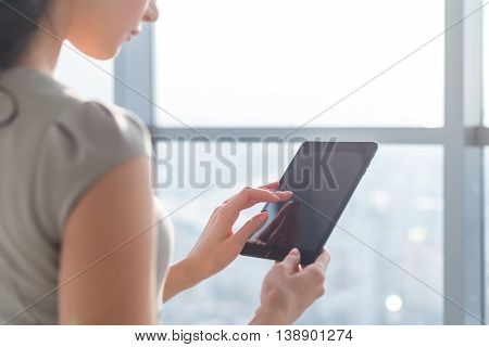 Side view photo of young female teleworker using tablet, searching and browsing information via wi-fi connection application in office or at home
