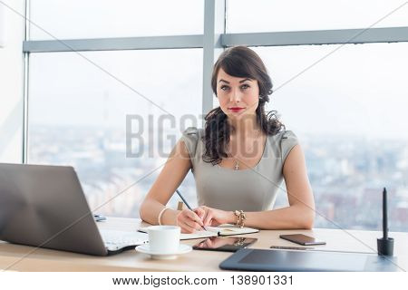 Side view portrait of a businesswoman sitting concentrated, writing, organizing her timetable in light office