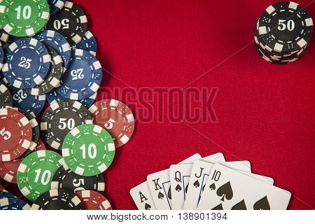 Gambling chips frame and flush royal on red card casino table background