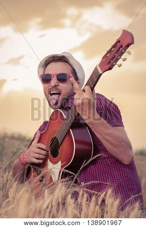 Portrait of young retro styled man playing acoustic guitar and showing finger in wheat field. Sun and clouds in the background. Music, art and lifestyle concepts.