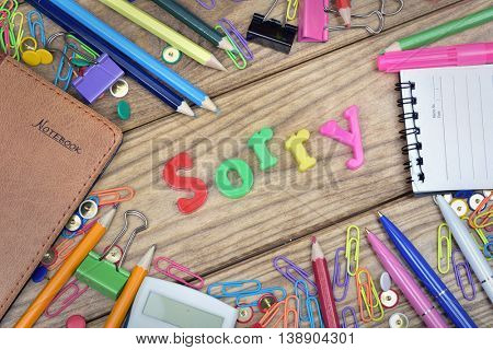 Sorry word and office tools on wooden table