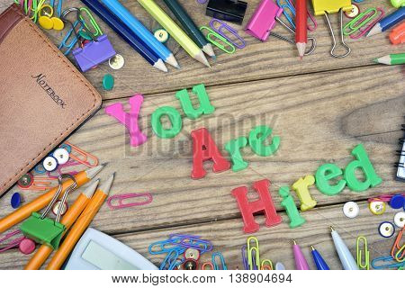 You are Hired word and office tools on wooden table