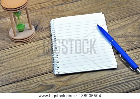 White notebook and pink shoes on wooden table