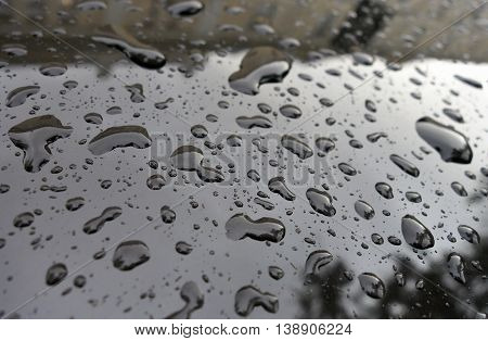 Raindrops on black car after heavy rain.