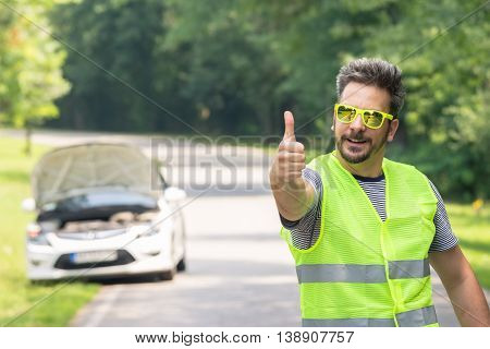 Young modern tourist man in reflective vest standing on the road and showing thumbs up. Car with opened hood in the background. Road assistance and safety measures concept.